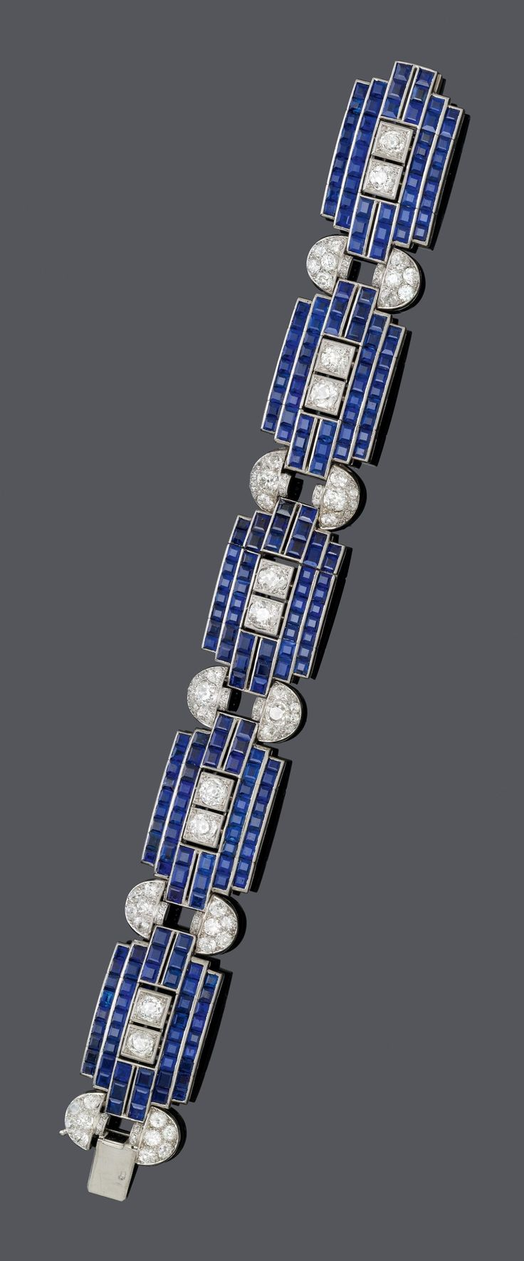 AN ART DECO PLATINUM, SAPPHIRE AND DIAMOND BRACELET, CIRCA 1930. Composed of five rectangular links, each set with 48 sapphire-carrés and two central circular-cut diamonds, joined by oval, diamond-set links.