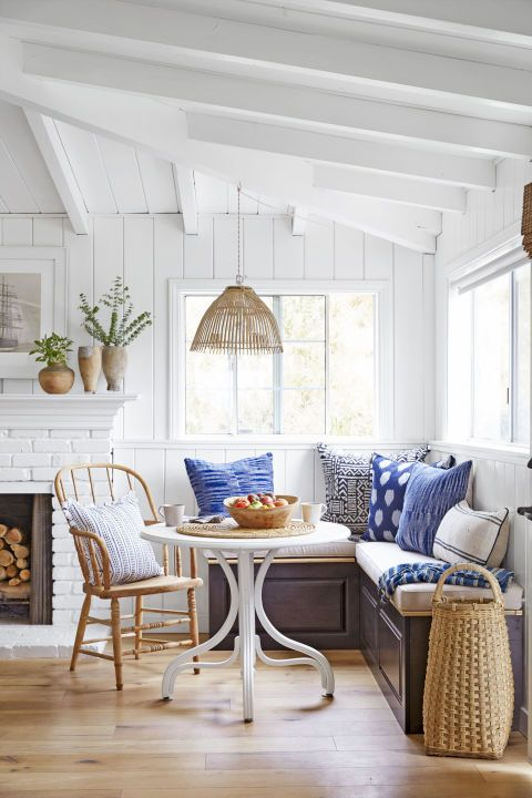 In this sunny nook, a built-in banquette maximizes seating and storage. And look closely: The built-ins are simply kitchen cabinets (leftover from the kitchen reno) turned on their sides. The pillows echo other pops of indigo throughout the room (X benches, ottomans), and the rattan pendant and basket provide texture.
