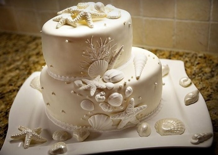Beach themed 2 tier oval ivory wedding cake with chocolate seashells and starfish  Image by Rae Letham