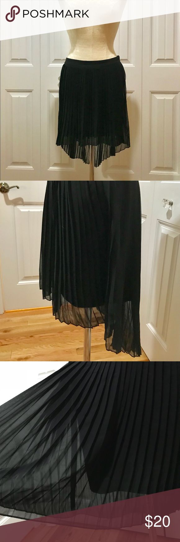 Black Pleated High-Low Skirt This is an American Eagle's high-low pleated black skirt. It has a shear pleated layer with a soft silky matte liner underneath. This skirt sits right at your waist and has a side zipper. It is a NEVER BEEN WORN piece. American Eagle Outfitters Skirts Asymmetrical