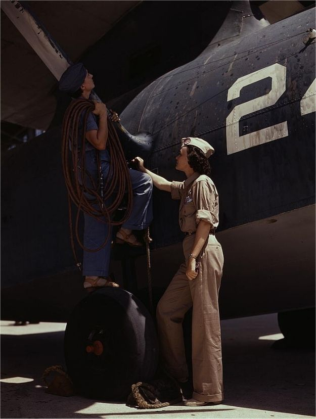 Cora Ann Bowen (left), employed as a cowler, at work at Corpus Christi Naval Air Base. Eloise J. Ellis (right) is a senior supervisor in the Assembly and Repairs department. Photographed by Howard R. Hallem in August 1942.