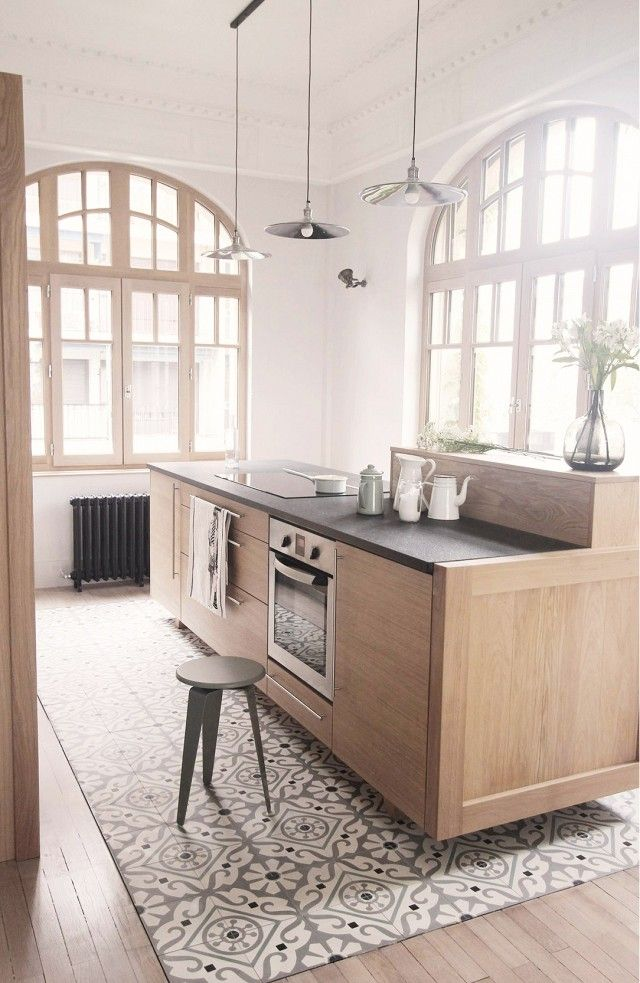 This is an interesting concept: use tile on parts of kitchen floor and bleed in with hard wood... Q: would it make your kitchen feel smaller?