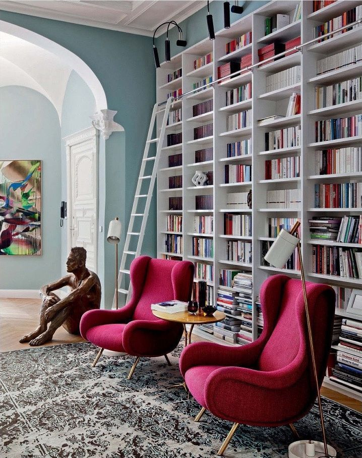 Indoors library with bright-coloured pink armchairs