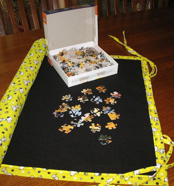 Here is a fun puzzle mat for the jigsaw puzzle lover! Everyone loves happy Snoopy and adorable Woodstock! The fabric is bright yellow with a dancing Snoopy and a cute, tiny Woodstock. It is accented by dots of black, navy and gray. The felt side is black. This will hold up to a 500 piece jigsaw puzzle.  If you need to move the puzzle before it is completed, you can roll it up and the pieces will cling to the felt and stay put until next time - expect to make a bit of adjustment to the…