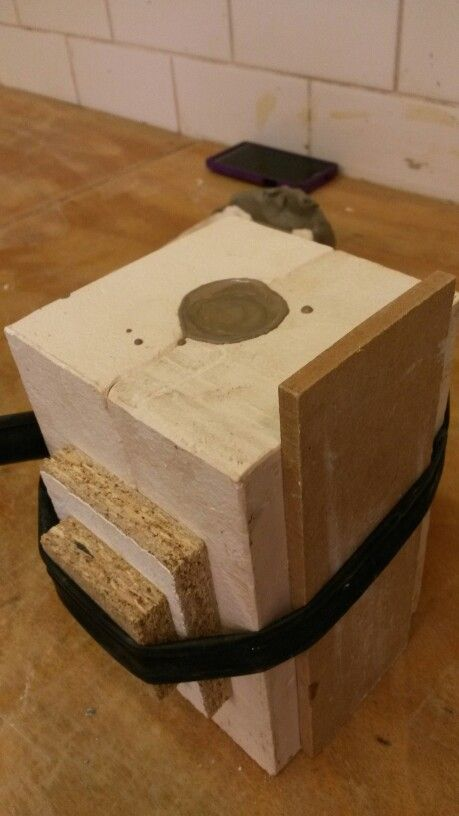 Mould with slip cast in it and an innertube round it and wooden blocks.