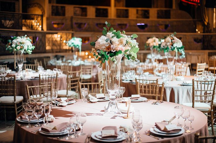 The decor of the guest tables. The central composition in high transparent vases with use using roses, carnations, hydrangeas, methiol, eucalyptus and salal