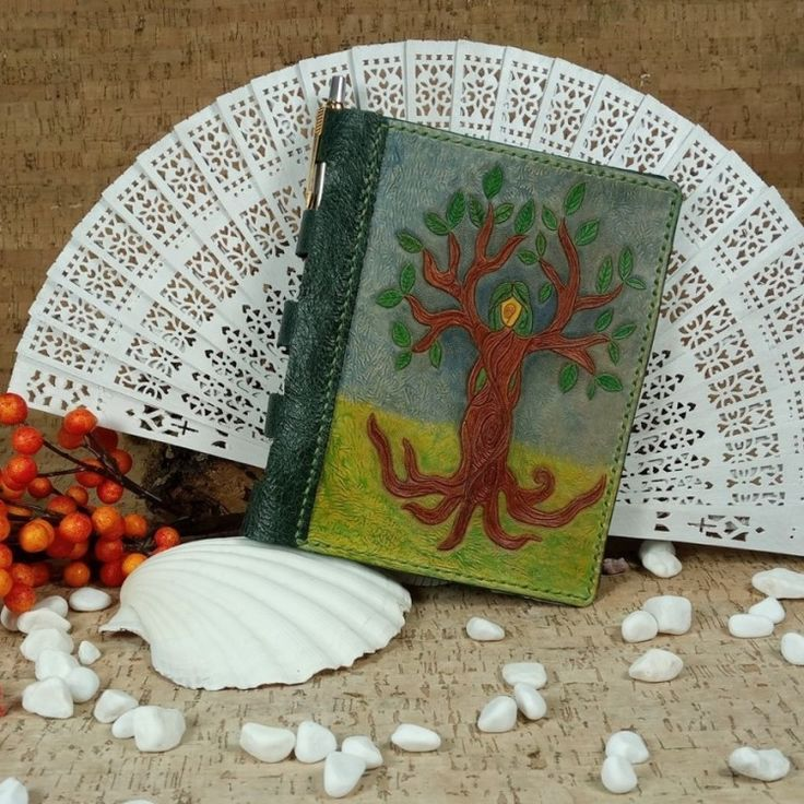 Tree of Life Refillable Notebook cover (No Shipping Costs - In stock) Custom handcrafted leather refillable notebook. Holds A6 size paper sheets and the hinged spine is made to hold a pen. The notebook cover is decorated on the front with a lovely hand carved, hand painted Tree of Life. On the inside is lined and Chicago screws are used to hold the A6 pages in place so that new pages can be added/replaced as needed.An amazing piece of art that you only find with hand crafted work…