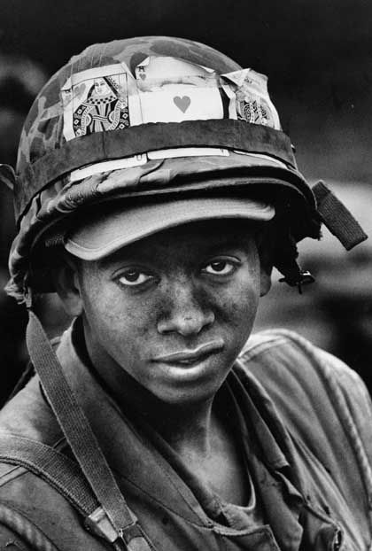 """Pfc. John L. Lewis decorates his helmet with good luck tokens. [Khe Sanh, February 1968.]"""" Life [Asia edition]. 18 Mar. 1968. cover."""