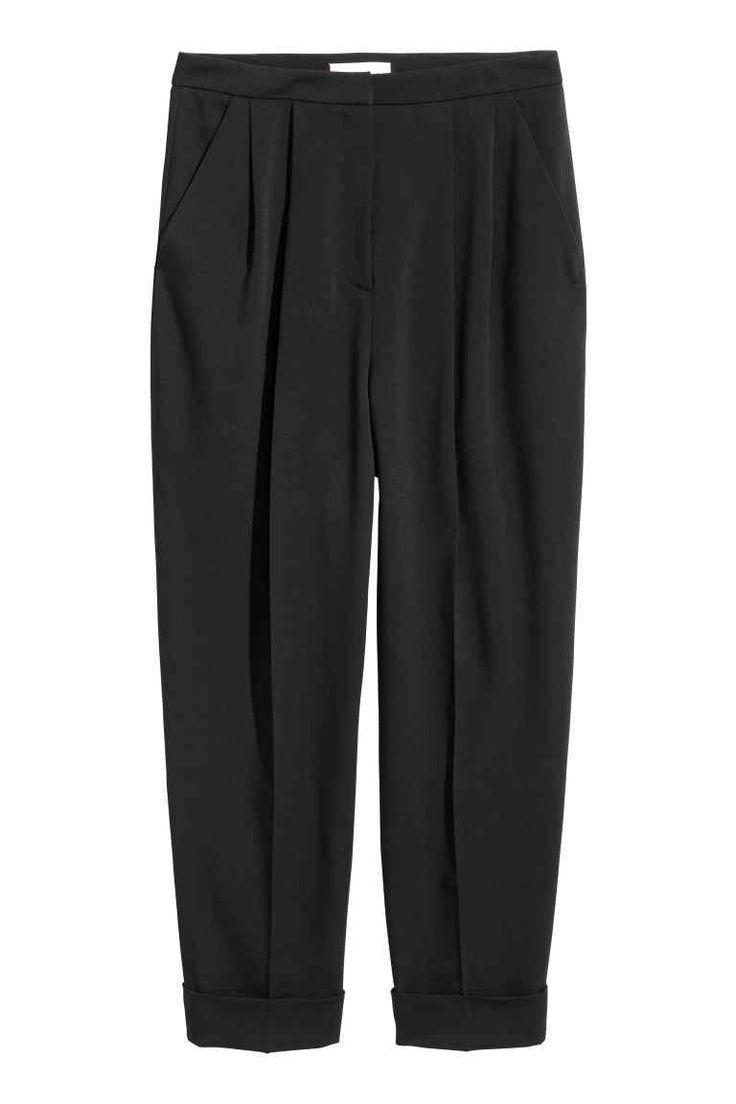 Spodnie z domieszką wełny: Spodnie z krepowanej mieszanki zawierającej wełnę. Wysoka talia z krytym zapięciem na haftkę i z zakładkami, kieszenie po bokach, z tyłu kieszenie z wypustką. Szerokie, zwężane nogawki do kostki z kantami i szerokim, przyszytym podwinięciem.