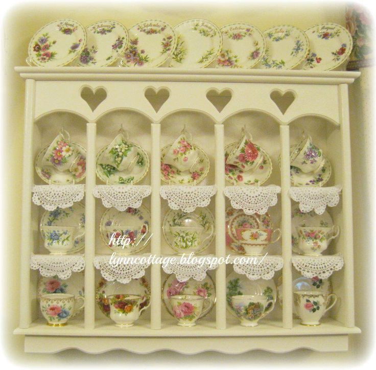 Antique tea cup collection displayed in a cute little cabinet.
