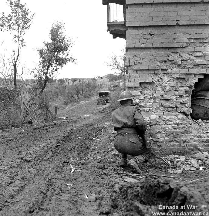 The Moro Valley - Private R.W. Hansen of The Loyal Edmonton Regiment watches warily down a street of San Leonardo Di Ortona covered by German fire.