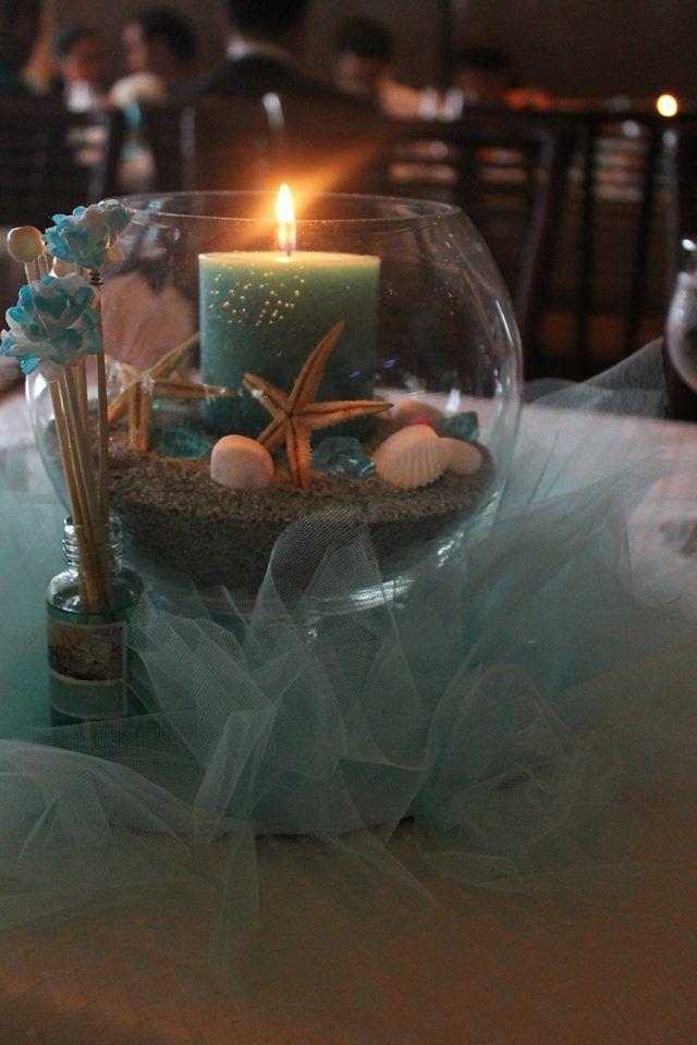 Centro de mesa de boda de cristal con arena con elementos marinos y velas. Tul turquesa de base