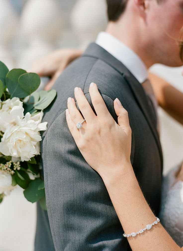 {{Bride's hand on groom's shoulder with classic, ivory bridal bouquet.}} Photography by Britta Marie Photography http://brittamariephotography.com/    Flowers by Pollen, pollenfloraldesign.com.