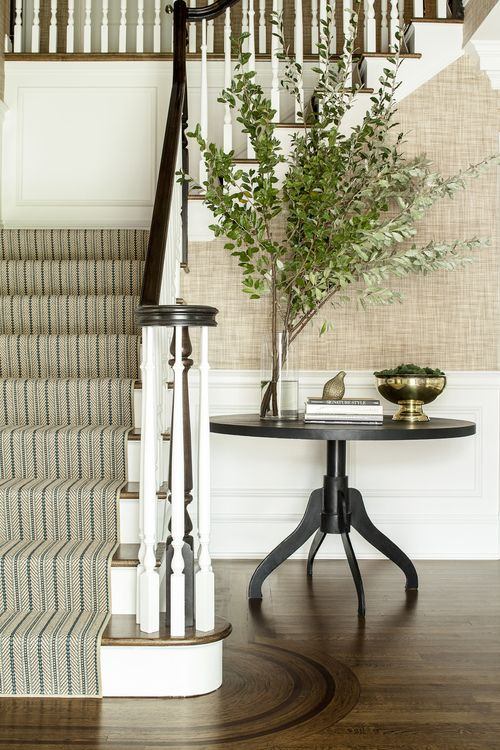 Traditional white and wood entrance hall. Love the swilling rounded wood pattern in the floor around the bottom step, grass cloth walls, and wood and white staircase.