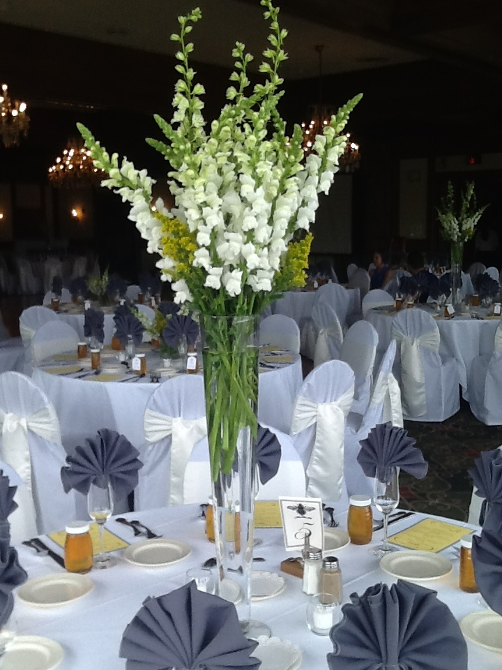 Tall centerpieces of white snapdragons and solidago