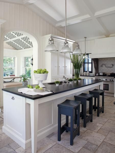 Sophisticated white kitchen with black counters from Canadian House and Home - lime green and blue painted stools are great accents.