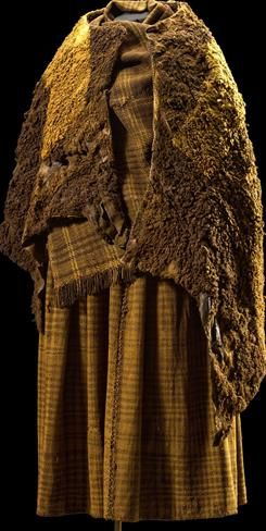 Iron Age female outfit complete. This is the real thing — a full costume retrieved from a Danish peat bog. The woman wore a thin linen undergarment, a woolen skirt & scarf, and then two lamb skin capes, the first turned wool side in, the second wool side out. The inner cape had a patch sewn on inside which was a comb, hairband and cord. She also wore woolen headband and a finger ring. The scarf was once red and the skirt blue