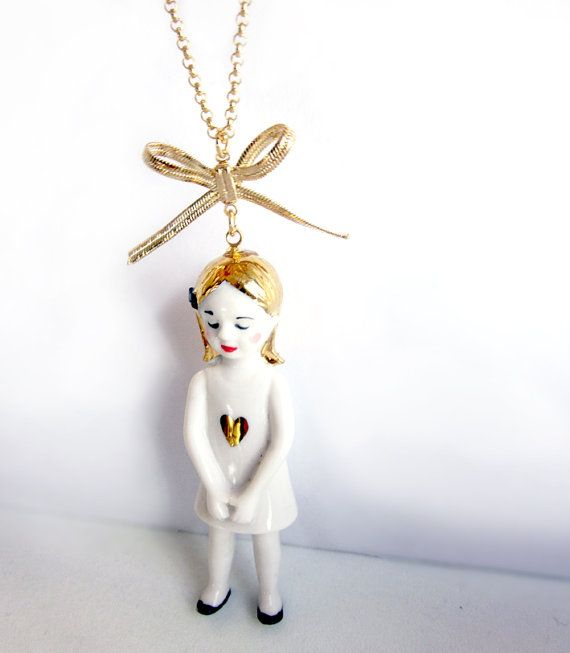 Eleonore is a lovely handmade and decorated porcelain doll (6 cm) on a 73cm gold plated chain. She comes with a little star or a little heart. Her