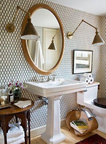 wallpaper in bathroom, gold oval mirror, wall sconces, pedestal sink