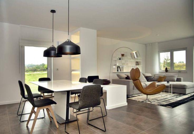 Großzügiges Wohnzimmer mit Sofa Drehsessel Bücherregal Teppich Gardinen Esstisch Lampe schwarz Parkett Holz Wand Weiß - Hommage198 - Hanlo Haus #LampEsstisch