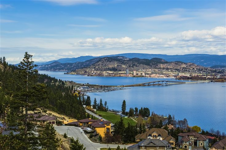 Explore Kelowna holidays and discover the best time and places to visit. | A kayaker paddles past scores of new tract houses on a hillside: it's an iconic image for ever-growing Kelowna, the unofficial 'capital' of the Okanagan and the sprawling center of all that's good and not-so-good with the region.Entering from the north, the ever-lengthening urban sprawl of tree-lined Hwy 97/Harvey Ave seems to go on forever. Once past the ceaseless waves of chains and strip malls, ...