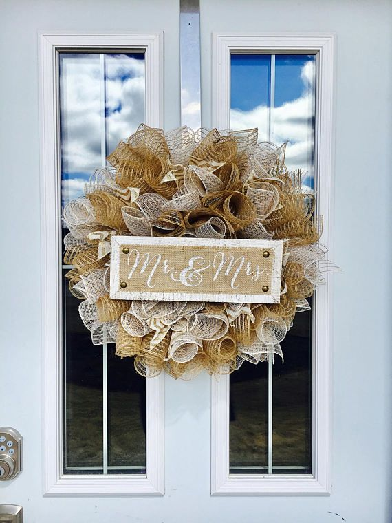 Individually cut pieces of white and beige deco mesh, scrunched and tied to a metal wreath form, creating this full elegant wreath. Accents of gold, chevron, burlap ribbon and a Mr & Mrs sign, complete this gorgeous piece of décor for that special day. Use it as a backdrop for your wedding, and hang it on your door. BONUS: The sign is removable and can be used for display with your wedding photos on a shelf or a feature wall. The neutral base colours on this wreath make it quite versatile...