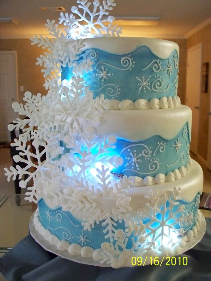 Fondant cake with blue shimmer dust. Snowflakes are royal icing. Fun cake to make. Glad I made lots of snowflakes cause they kept breaking. Some of the broken ones were great for filling in spots and covering edges