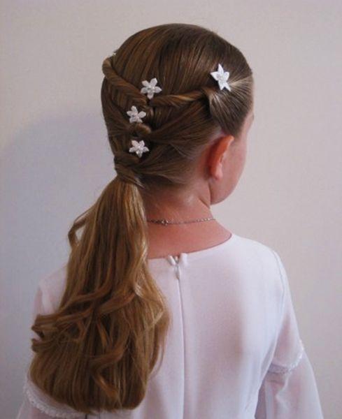 Peinado para niña con raya en medio recogido con tiras torcidas adornadas con pequeñas flores y coleta baja.