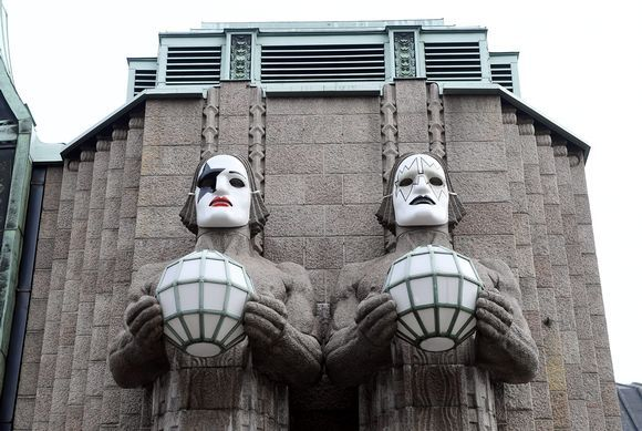"""""""The makeup-wearing band Kiss has arrived to Helsinki - or at least their likenesses have. The huge, lamp-holding statues at the entrance of Helsinki Central railway station are now wearing Kiss face masks which were painted by four local fans."""" Yle News 28.4.2017"""