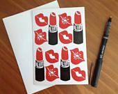 Labios de rojo y tarjeta de felicitación del lápiz labial (en blanco)