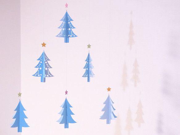 モビール - クリスマス・ツリー(blue) -小さなモミの木の集まりです。モミの木の上にはキラキラお星様が輝いています。ブルーと薄青の組み合わせです。一つでも可愛いけど、ピンクやグリーンと並べても可愛いんですよ♪=== 素材 ===・紙・ワイヤー・糸・カシメ玉・木工用ボンド=== サイズ ===約35cm X 約40cm(吊り下げ部分は含みません)※なるべく作品に近い色になるよう写真を撮っていますが、光の加減等により忠実には再現できていない場合があります。こちらの作品は4枚目の写真が一番近いイメージになります。☆ハンドメイドクリスマス2014☆2014冬ハンドメイド