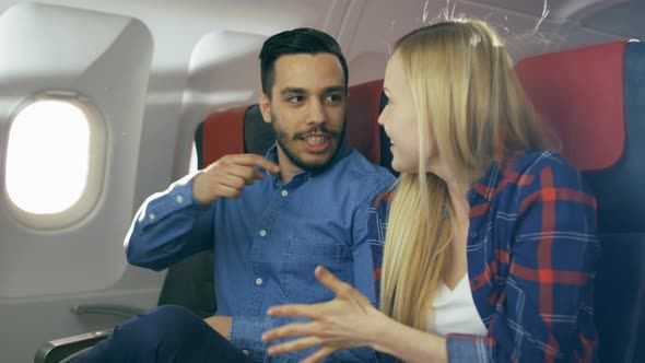 On a Plane Flight Handsome Hispanic Man Tells Funny Story to His Beautiful Blonde Girlfriend.