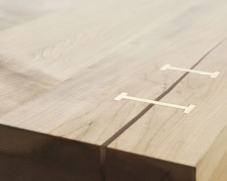 Detail showing edge of custom coffee table with natural crack in maple wood table top, stabilized by solid brass stitches.