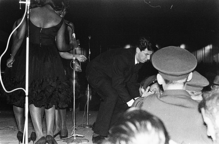 Policie officers and steward trying (in vain) to calm audience at Ray Charles concert at the Amsterdam Rai. The Raelettes (Darlene McCrea looking at the scene) sing on. Photo by Hugo van Gelderen, on May 11, 1963.