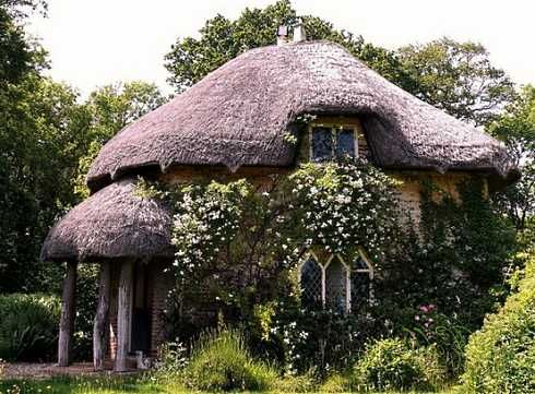 This  romantic cottage is similar in design to some of the fairy-  tale cottages found at Blaise Hamlet in northwest Bristol, England. Peeking out from under a heavy thatch roof and ivy-draped walls are little windows with diamond panes.