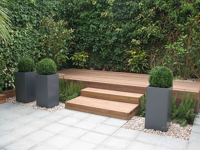 Ground level patio with steps up to raised deck with shed for Garden design decking areas