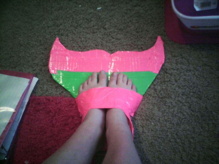 Diy monofin. Just trace your feet and your fin shape onto cardboard, then cut it out and duck tape the whole thing, then put your feet on for sizing. Fold a strand of duck tape , wrap it over the top of your feet, then secure with more tape. Add another small piece to the back of the foot strap so your heels and ankles will push agai nst it to keep your feet from sliding out. Im going to swim in it for the first time at a family 4th of July party! #DIY #mermaid # monofin #4th of July