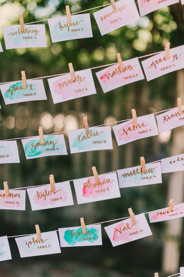 watercolor escort cards - photo by Lillywhite Photography http://ruffledblog.com/wearing-her-sisters-wedding-dress