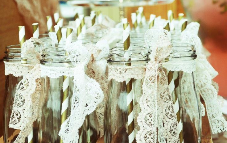 """Glass """"milk"""" bottles for the lemonade , with vintage lace trimmings and gold and white striped paper straws"""