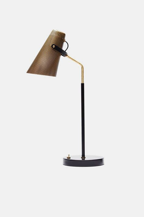 """Inspired by artisan craftsmanship as well as industrial modes of fabrication, Atelier de Troupe looks for the familiar and the timeless in design. The studio's lighting collection includes this table lamp. Handmade in Los Angeles, it combines a perforated brass shade and brass stem with a powder-coated black metal base and """"spur""""—éperon in French."""