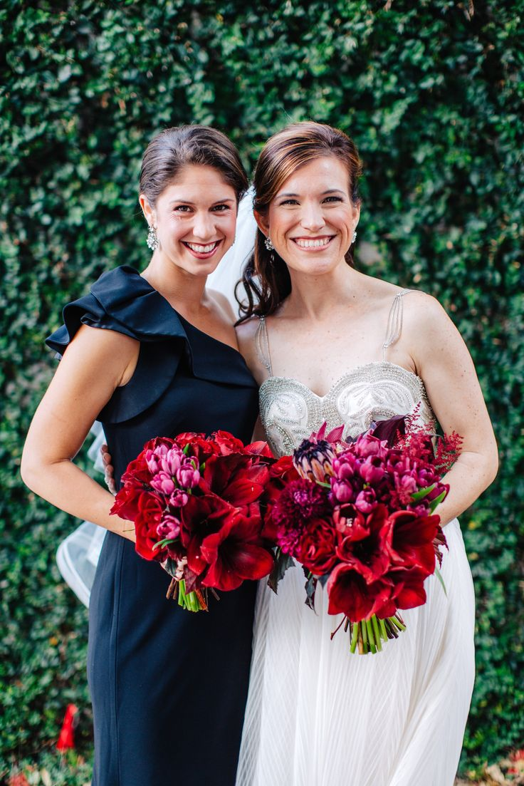 bride and her bridesmaid hold their modern and glamorous bouquets of red amaryllis, burgundy mini calla lily, black parrot tulips, burgundy astilbe, deep red roses, chocolate cymbidium orchids and pink mink protea and burgundy dahlias and begonia leaf.