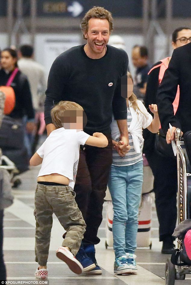 Home time: Chris Martin and his children Apple and Moses looked excited as they made their way through the airport