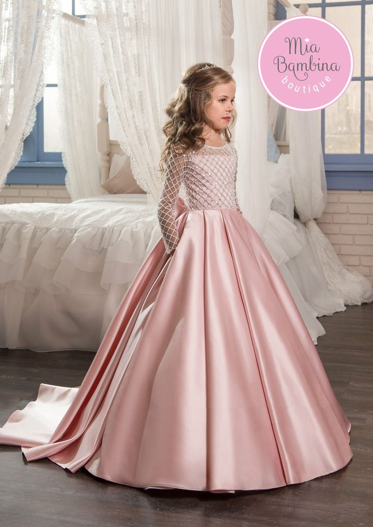 This chic Toronto flower girl dress is a long satin ball gown for vintage-inspired weddings. It features a long-sleeved top embroidered with textured lattice lace all-over. Shining sequins make the to