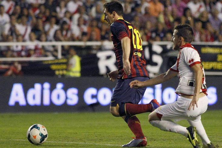 """El delantero argentino del FC Barcelona Lionel Messi controla el balón seguido por el defensa del Rayo VAllecano Roberto Román, """"Tito"""""""