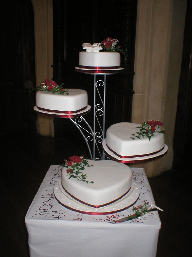 Four tier heart shaped Wedding cake decorated with handmade sprays of roses, rose leaves and trailing ivy.