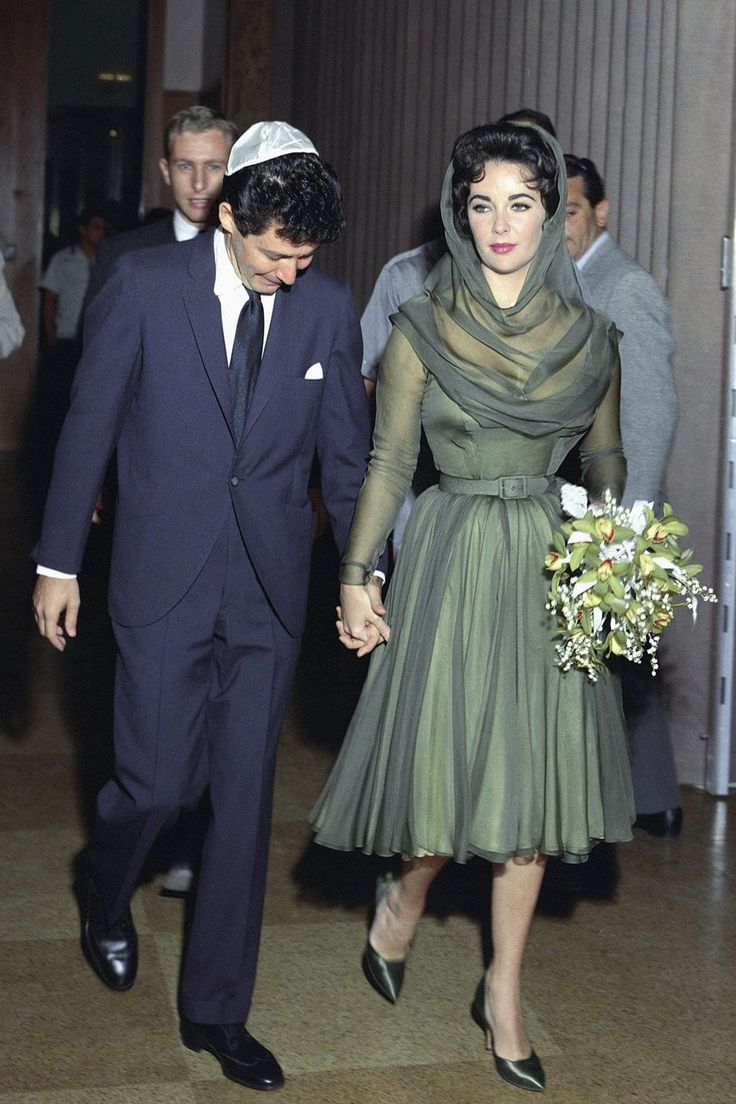 In May 1959, when Elizabeth Taylor married her fourth husband, singer Eddie Fisher - who left his wife Debbie Reynolds to marry Taylor – she wore a short, hooded, forest green dress with matching shoes and a bouquet made up of orchids and baby's breath. Taylor's third husband, producer Mike Todd – with whom she had a daughter, Liza – had died in a plane crash in March 1958.    Following her divorce from Fisher, Liz went on to marry (and divorce) Richard Burton twice before two further…