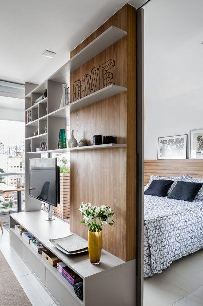 A estante com prateleiras vazadas não pesa no visual e ainda comunica os ambientes. O suporte da TV gira a fim de que ela se volte tanto para o quarto como para a sala.
