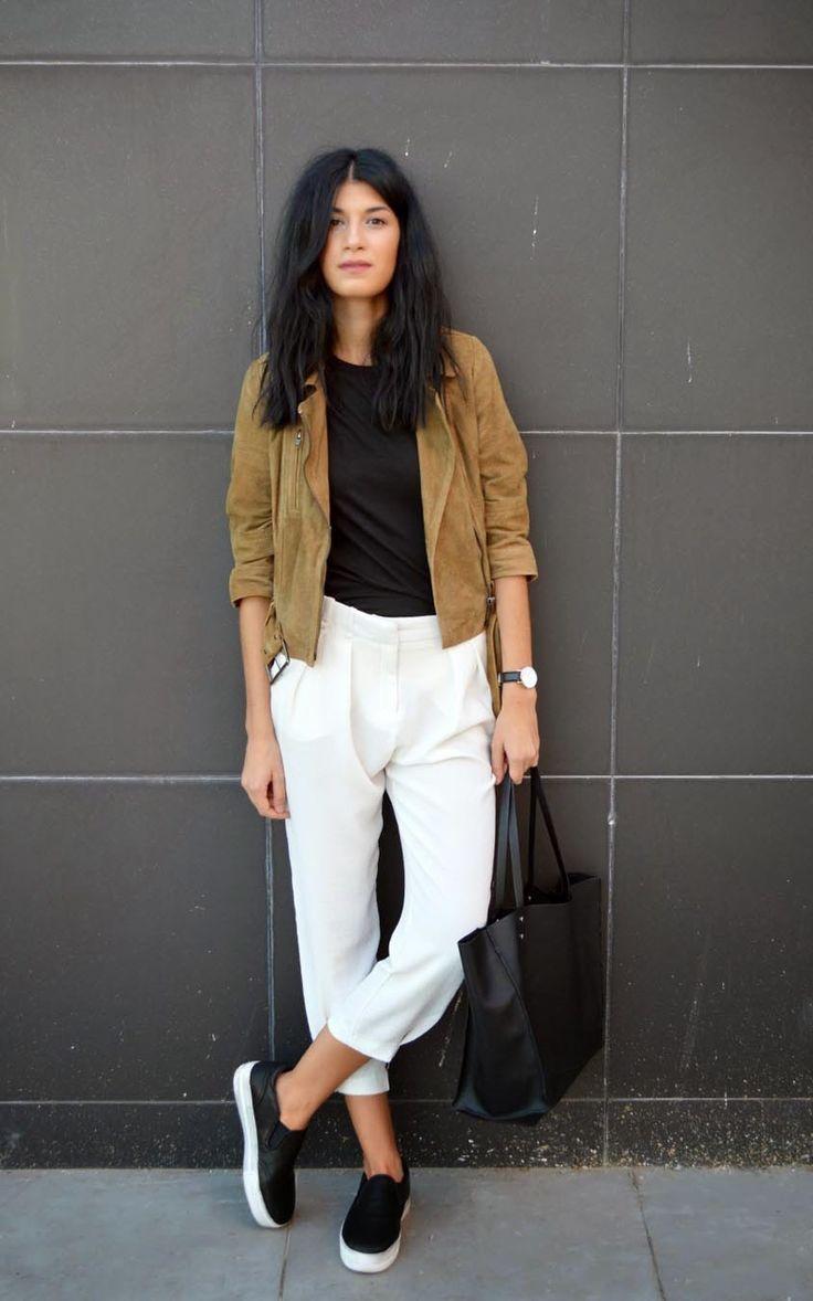 Look básico com t-shirt preta, jaqueta de camurça, calça cropped branca e tênis slip on preto