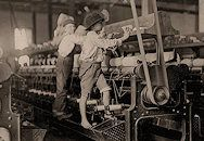 """Textile mill. """"Some boys and girls were so small they had to climb up on to the spinning frame to mend broken threads and to put back the empty bobbins. Bibb Mill No. 1. Macon, Georgia."""" Photograph and original caption by Lewis Hine"""