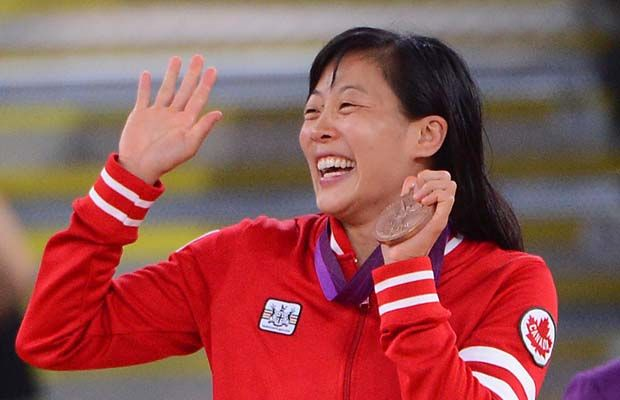 Carol Huynh of Canada celebrates with her bronze medal in women's 48-kg. freestyle wrestling at the London 2012 Olympic Games on Wednesday, Aug. 8, 2012.